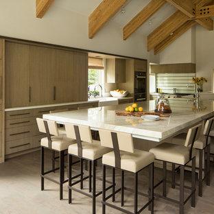 他の地域のラスティックスタイルのおしゃれなアイランドキッチン (エプロンフロントシンク、フラットパネル扉のキャビネット、中間色木目調キャビネット、パネルと同色の調理設備、無垢フローリング、白いキッチンカウンター、珪岩カウンター、マルチカラーのキッチンパネル、ガラス板のキッチンパネル) の写真