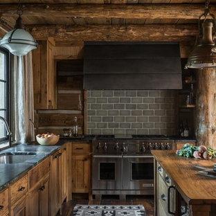 Idée de décoration pour une cuisine ouverte chalet en L avec un électroménager en acier inoxydable, un îlot central, un évier encastré, des portes de placard en bois brun, une crédence grise, une crédence en carrelage métro et un plan de travail noir.