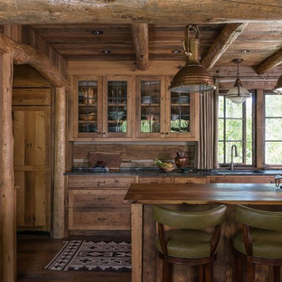 Rustic kitchen photos - Inspiration for a rustic dark wood floor and brown floor kitchen remodel in Other with glass-front cabinets, soapstone countertops, wood backsplash, an island, an undermount sink, medium tone wood cabinets and black countertops