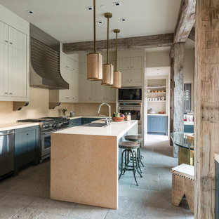 Kitchen - mid-sized rustic limestone floor kitchen idea in Other with a double-bowl sink, beige cabinets, granite countertops and an island