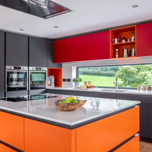 Photo of a midcentury l-shaped kitchen in Gloucestershire with a submerged sink, flat-panel cabinets, grey cabinets, window splashback, stainless steel appliances, medium hardwood flooring, an island, brown floors and white worktops.