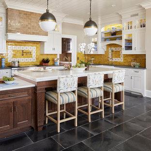 ニューヨークのカントリー風おしゃれなキッチン (エプロンフロントシンク、シェーカースタイル扉のキャビネット、白いキャビネット、黄色いキッチンパネル、シルバーの調理設備) の写真