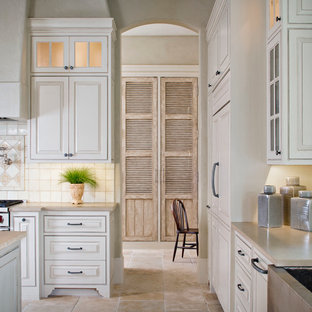 This is an example of a traditional l-shaped eat-in kitchen in Houston with a farmhouse sink, limestone benchtops, white splashback, stainless steel appliances, raised-panel cabinets, beige cabinets and stone tile splashback.