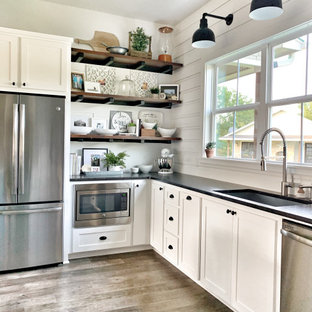 Large country u-shaped eat-in kitchen with an undermount sink, shaker cabinets, white cabinets, granite benchtops, white splashback, shiplap splashback, stainless steel appliances, vinyl floors, with island, grey floor and black benchtop.