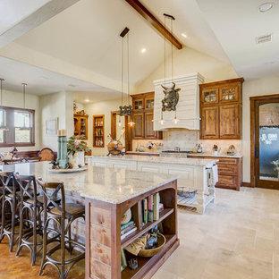 ダラスのサンタフェスタイルのおしゃれなキッチン (エプロンフロントシンク、レイズドパネル扉のキャビネット、茶色いキャビネット、ベージュキッチンパネル、シルバーの調理設備の、ベージュの床) の写真