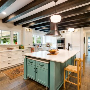 Cottage l-shaped medium tone wood floor kitchen photo in Other with a farmhouse sink, shaker cabinets, white cabinets, marble countertops, multicolored backsplash, stainless steel appliances and two islands