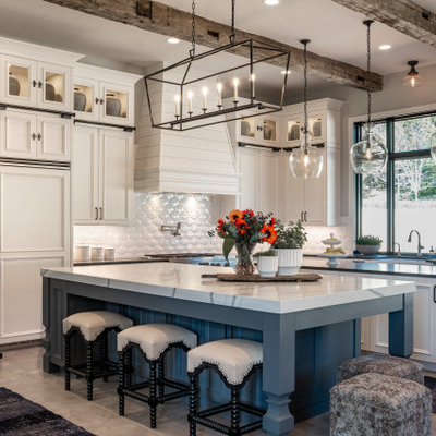 Country l-shaped gray floor kitchen photo with recessed-panel cabinets, white cabinets, white backsplash, paneled appliances, two islands and white countertops