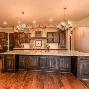 Offene, Große Urige Küche mit Unterbauwaschbecken, profilierten Schrankfronten, dunklen Holzschränken, Granit-Arbeitsplatte, Küchenrückwand in Weiß, Rückwand aus Steinfliesen, Küchengeräten aus Edelstahl, dunklem Holzboden und Kücheninsel in Austin