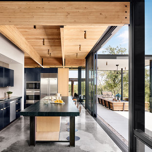 Large modern kitchen in Austin with flat-panel cabinets, limestone benchtops, beige splashback, cement tile splashback, stainless steel appliances, concrete floors, with island and grey floor.