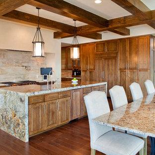オースティンの中サイズのモダンスタイルのおしゃれなキッチン (アンダーカウンターシンク、シェーカースタイル扉のキャビネット、中間色木目調キャビネット、御影石カウンター、ベージュキッチンパネル、トラバーチンの床、シルバーの調理設備の、濃色無垢フローリング、茶色い床) の写真