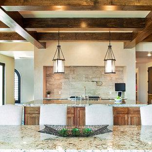 オースティンの中くらいのモダンスタイルのおしゃれなキッチン (アンダーカウンターシンク、シェーカースタイル扉のキャビネット、中間色木目調キャビネット、御影石カウンター、ベージュキッチンパネル、トラバーチンのキッチンパネル、シルバーの調理設備、濃色無垢フローリング、茶色い床) の写真