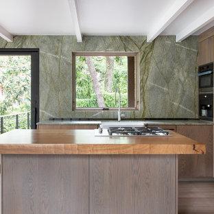 オースティンの小さいモダンスタイルのおしゃれなキッチン (エプロンフロントシンク、フラットパネル扉のキャビネット、中間色木目調キャビネット、御影石カウンター、緑のキッチンパネル、石スラブのキッチンパネル、シルバーの調理設備、淡色無垢フローリング、グレーの床、緑のキッチンカウンター) の写真