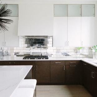 Inredning av ett modernt vit vitt kök, med en undermonterad diskho, luckor med profilerade fronter, vita skåp, kaklad bänkskiva, stänkskydd med metallisk yta, stänkskydd i porslinskakel, rostfria vitvaror, ljust trägolv, en köksö och beiget golv