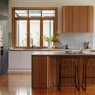 Mid-sized midcentury l-shaped eat-in kitchen in Adelaide with an undermount sink, flat-panel cabinets, black cabinets, solid surface benchtops, grey splashback, stone slab splashback, panelled appliances, light hardwood floors, with island, brown floor and grey benchtop.
