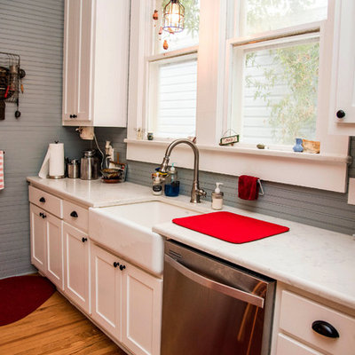 Mid-sized country galley dark wood floor and brown floor open concept kitchen photo in Austin with a farmhouse sink, shaker cabinets, white cabinets, quartz countertops, gray backsplash, stainless steel appliances and an island