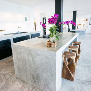 Mid-sized beach style open concept kitchen inspiration - Mid-sized coastal single-wall concrete floor and gray floor open concept kitchen photo in Other with a drop-in sink, flat-panel cabinets, dark wood cabinets, concrete countertops, white backsplash, limestone backsplash, paneled appliances, an island and gray countertops