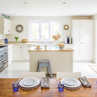 Large coastal l-shaped kitchen/diner in Buckinghamshire with a belfast sink, white cabinets, grey splashback, ceramic splashback, ceramic flooring, an island, white floors, shaker cabinets, wood worktops and stainless steel appliances.