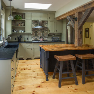 Large farmhouse kitchen ideas - Large farmhouse l-shaped light wood floor kitchen photo in Boston with a farmhouse sink, beaded inset cabinets, green cabinets, soapstone countertops, brown backsplash, ceramic backsplash, stainless steel appliances and an island
