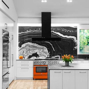 Retro Küche in L-Form mit Unterbauwaschbecken, flächenbündigen Schrankfronten, grauen Schränken, Küchenrückwand in Schwarz, Rückwand aus Stein, Küchengeräten aus Edelstahl, hellem Holzboden, Kücheninsel und beigem Boden in Houston