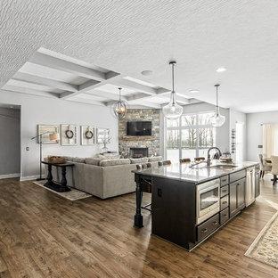 コロンバスのカントリー風おしゃれなキッチン (ダブルシンク、フラットパネル扉のキャビネット、黒いキャビネット、シルバーの調理設備、無垢フローリング、茶色い床、グレーのキッチンカウンター) の写真