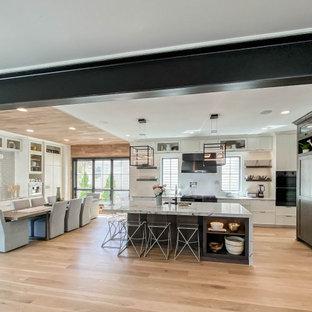 Idéer för att renovera ett mycket stort industriellt vit vitt kök och matrum, med en nedsänkt diskho, skåp i shakerstil, vita skåp, bänkskiva i kvarts, grått stänkskydd, stänkskydd i tunnelbanekakel, svarta vitvaror, ljust trägolv och en köksö