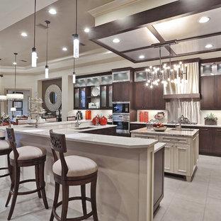 タンパの大きいコンテンポラリースタイルのおしゃれなキッチン (アンダーカウンターシンク、フラットパネル扉のキャビネット、濃色木目調キャビネット、人工大理石カウンター、ベージュキッチンパネル、ガラスタイルのキッチンパネル、パネルと同色の調理設備、トラバーチンの床) の写真