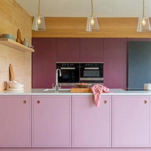 Foto på ett litet funkis vit kök, med en enkel diskho, släta luckor, lila skåp, bänkskiva i kvartsit, rostfria vitvaror, mellanmörkt trägolv, en köksö och brunt golv
