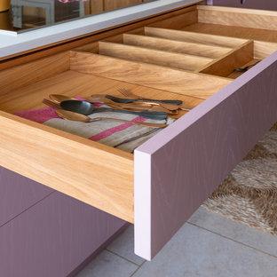 Idée de décoration pour une petite cuisine design avec un évier 1 bac, un placard à porte plane, des portes de placard violettes, un plan de travail en quartz, un électroménager en acier inoxydable, un sol en bois brun, un îlot central, un sol marron et un plan de travail blanc.