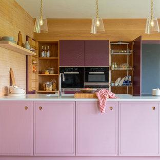 Bild på ett litet funkis vit vitt parallellkök, med en enkel diskho, släta luckor, lila skåp, bänkskiva i kvartsit, rostfria vitvaror, mellanmörkt trägolv, brunt golv och en halv köksö
