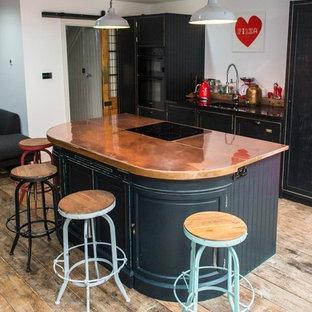 Offene, Zweizeilige, Große Urige Küche mit Einbauwaschbecken, Schrankfronten im Shaker-Stil, Schränken im Used-Look, Kupfer-Arbeitsplatte, Elektrogeräten mit Frontblende, dunklem Holzboden und Kücheninsel in London