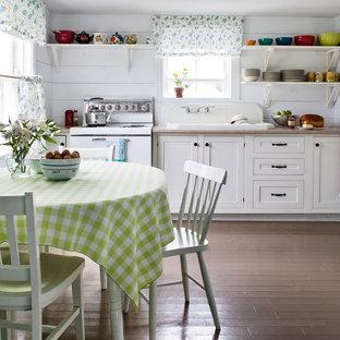 Shabby chic-inspirerad inredning av ett kök och matrum, med en nedsänkt diskho, luckor med profilerade fronter, vita skåp och vita vitvaror