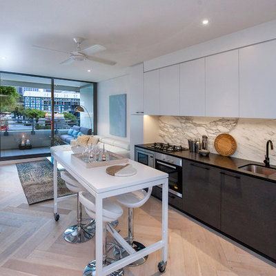 Inspiration for a mid-sized contemporary single-wall light wood floor open concept kitchen remodel in Sydney with an undermount sink, flat-panel cabinets, white cabinets, white backsplash, stainless steel appliances, an island, marble countertops and marble backsplash