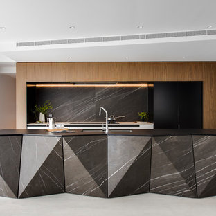Inspiration for a large contemporary galley kitchen pantry in Sydney with a double-bowl sink, flat-panel cabinets, white cabinets, recycled glass benchtops, grey splashback, marble splashback, black appliances, porcelain floors, with island, grey floor and black benchtop.
