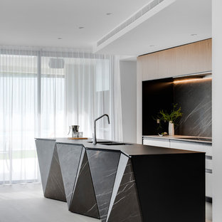 Large contemporary galley kitchen pantry in Sydney with a double-bowl sink, flat-panel cabinets, white cabinets, recycled glass benchtops, grey splashback, marble splashback, black appliances, porcelain floors, with island, grey floor and black benchtop.