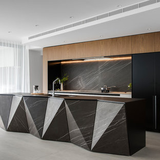 This is an example of a large contemporary galley kitchen pantry in Sydney with a double-bowl sink, flat-panel cabinets, white cabinets, recycled glass benchtops, grey splashback, marble splashback, black appliances, porcelain floors, with island, grey floor and black benchtop.
