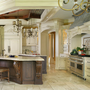 This is an example of a large traditional l-shaped eat-in kitchen in New York with a farmhouse sink, beaded inset cabinets, white cabinets, limestone benchtops, beige splashback, stone tile splashback, panelled appliances, travertine floors and multiple islands.