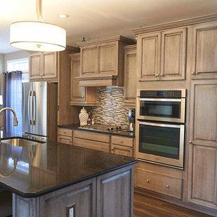 Offene, Einzeilige, Mittelgroße Rustikale Küche mit dunklem Holzboden, Unterbauwaschbecken, profilierten Schrankfronten, beigen Schränken, Granit-Arbeitsplatte, bunter Rückwand, Rückwand aus Stäbchenfliesen, Küchengeräten aus Edelstahl, Kücheninsel, braunem Boden und schwarzer Arbeitsplatte in Sonstige