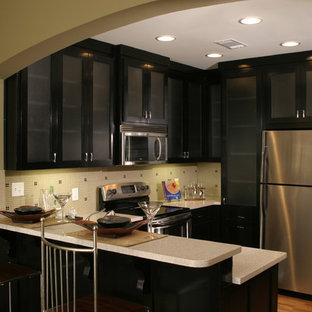 This is an example of a small transitional u-shaped open plan kitchen in Atlanta with a double-bowl sink, shaker cabinets, black cabinets, recycled glass benchtops, beige splashback, glass tile splashback, stainless steel appliances, medium hardwood floors, no island, brown floor and grey benchtop.