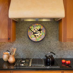 アルバカーキの広いサンタフェスタイルのおしゃれなキッチン (エプロンフロントシンク、シェーカースタイル扉のキャビネット、中間色木目調キャビネット、御影石カウンター、グレーのキッチンパネル、石タイルのキッチンパネル、シルバーの調理設備) の写真