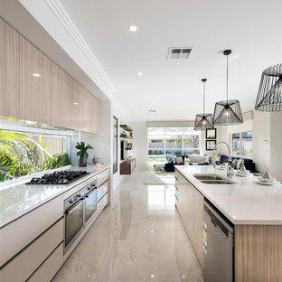 Diseño de cocina de galera, contemporánea, grande, abierta, con fregadero de doble seno, puertas de armario de madera oscura, encimera de cuarzo compacto, electrodomésticos de acero inoxidable, suelo de baldosas de porcelana y una isla
