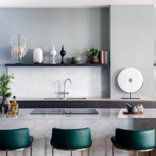 Zweizeilige, Große Moderne Wohnküche mit flächenbündigen Schrankfronten, Küchenrückwand in Weiß, Kücheninsel, weißer Arbeitsplatte, Unterbauwaschbecken, dunklen Holzschränken, Marmor-Arbeitsplatte, Rückwand aus Marmor, Küchengeräten aus Edelstahl, hellem Holzboden, grauem Boden und Kassettendecke in London
