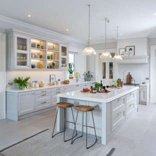 Design ideas for a traditional u-shaped kitchen/diner in Other with a submerged sink, recessed-panel cabinets, grey cabinets, white splashback, integrated appliances, an island, beige floors and white worktops.