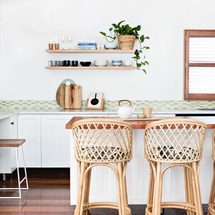Inspiration for a beach style l-shaped kitchen in Wollongong with shaker cabinets, white cabinets, wood benchtops, green splashback, mosaic tile splashback, medium hardwood floors, with island, brown floor and brown benchtop.