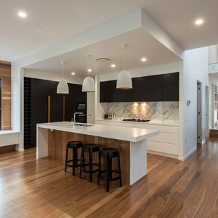 Photo of a contemporary galley kitchen in Brisbane with black cabinets, grey splashback, marble splashback, medium hardwood floors, with island, white benchtop, a double-bowl sink, flat-panel cabinets, black appliances and brown floor.