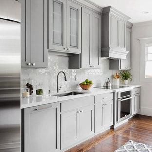 Bild på ett stort vintage kök, med en undermonterad diskho, skåp i shakerstil, grå skåp, bänkskiva i koppar, vitt stänkskydd, stänkskydd i keramik, rostfria vitvaror, mörkt trägolv och en köksö