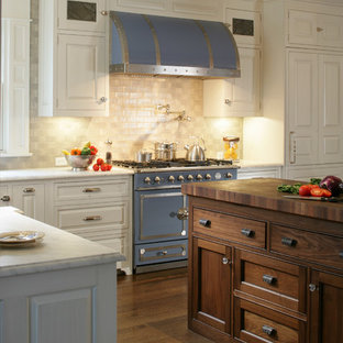 Elegant l-shaped eat-in kitchen photo in New York with a farmhouse sink, raised-panel cabinets, white cabinets, marble countertops, gray backsplash, ceramic backsplash and colored appliances