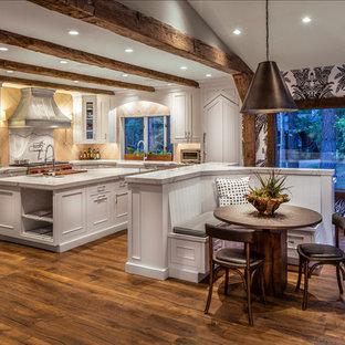 Exempel på ett rustikt vit vitt kök, med en rustik diskho, luckor med infälld panel, vita skåp, vitt stänkskydd, stänkskydd i sten, rostfria vitvaror, flera köksöar, bänkskiva i kvartsit, mörkt trägolv och brunt golv