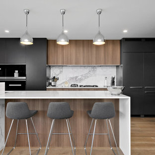 Inspiration for a large contemporary galley open plan kitchen in Sydney with an integrated sink, black cabinets, quartz benchtops, grey splashback, marble splashback, stainless steel appliances, medium hardwood floors, with island, brown floor, white benchtop and flat-panel cabinets.