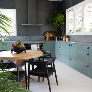 Photo of a medium sized contemporary l-shaped kitchen/diner in Sydney with a submerged sink, flat-panel cabinets, green cabinets, engineered stone countertops, grey splashback, slate splashback, stainless steel appliances, painted wood flooring, white floors and grey worktops.