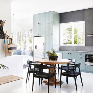 Design ideas for a mid-sized tropical l-shaped eat-in kitchen in Sydney with an undermount sink, flat-panel cabinets, quartz benchtops, grey splashback, slate splashback, stainless steel appliances, painted wood floors, white floor, grey benchtop and blue cabinets.